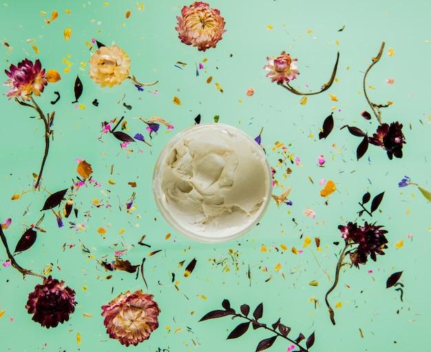 Herbe sèche de bellis avec des fleurs et de la crème de soin de la peau sur fond vert isolé. sans ombres