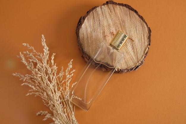 Herbe sèche et bouteille de parfum rectangulaire avec un capuchon en or sur une coupe à la scie ronde d'un podium d'arbre sur fond marron