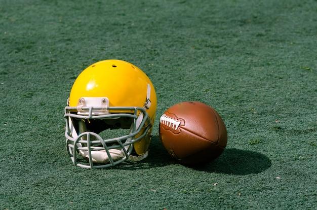 Herbe de stade avec casque de football et ballon dessus. convient pour le fond.