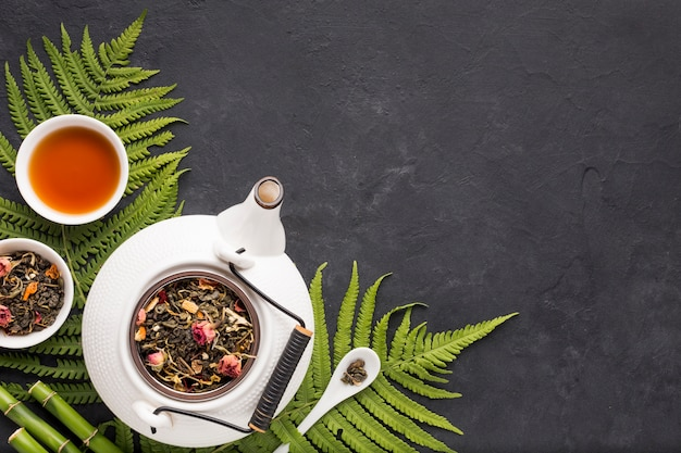Herbe de thé séchée avec des feuilles de fougère et un bâton de bambou sur un fond texturé noir