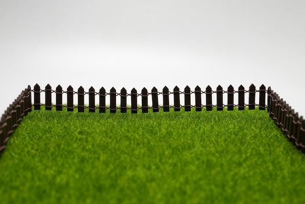 Herbe verte et clôture isolée sur fond blanc.