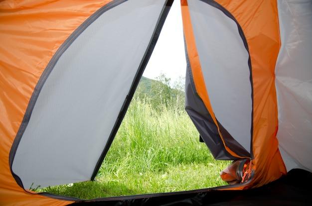 L'herbe verte des montagnes vue de l'intérieur d'une tente de randonnée