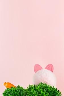 Herbe verte, oreilles de lapin et carotte sur fond rose. jardin ou prairie de printemps.