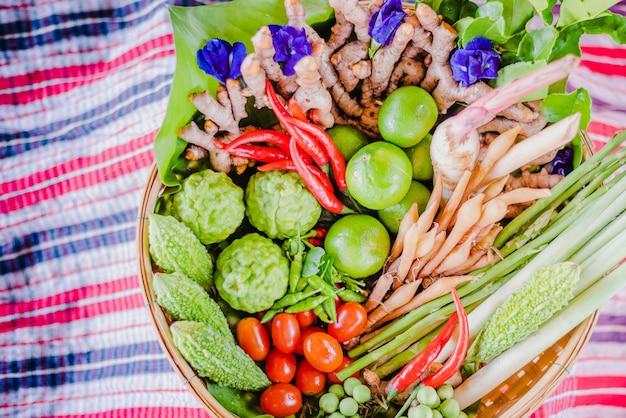 Herbes asiatiques fraîches et aliments épicés dans un panier en bambou