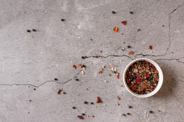 Herbes et condiments sur table en pierre noire.
