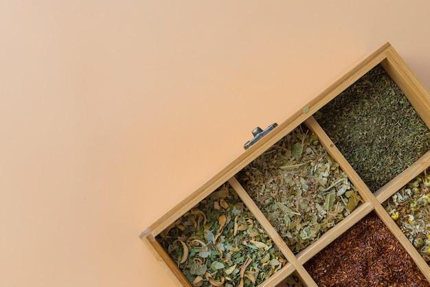 Herbes avec cuillère en bois sur fond marron