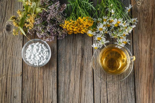 Herbes curatives et bol de pilules sur table en bois