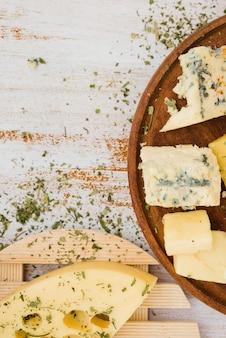 Herbes avec du fromage sur les montagnes russes en bois sur la planche
