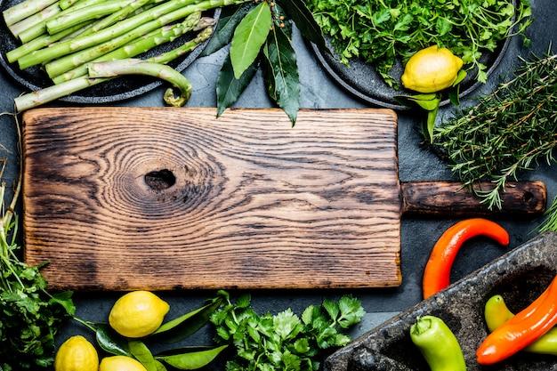 Herbes et épices autour d'une planche à découper en bois.