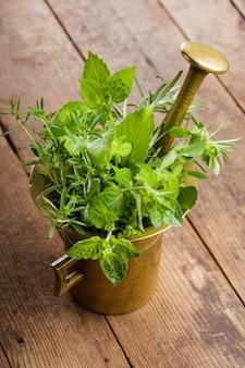 Herbes fraîches dans le mortier de cuivre sur la table