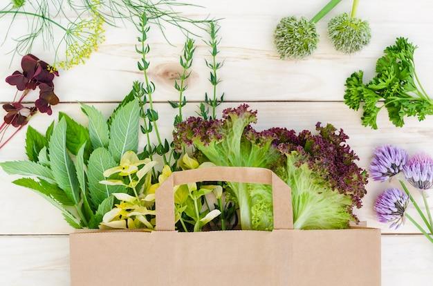 Herbes fraîches dans un sac en papier écologique sur table en bois. livraison de nourriture.