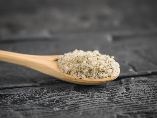 Herbes avec gros sel de mer en cuillère sur table en bois foncé.