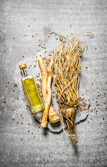 Herbes à l'huile d'olive dans une bouteille sur pierre se tiennent sur une table en pierre. vue de dessus