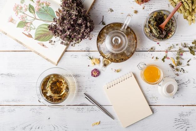 Herbes médicinales avec recette sur table en bois. mise à plat