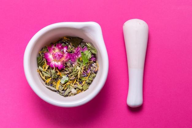 Herbes en mortier de porcelaine sur table colorée
