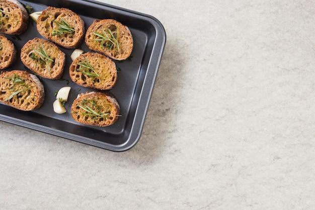 Herbes de romarin sur du pain grillé dans une plaque à pâtisserie