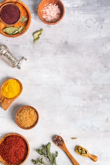 Herbes séchées et épices en cuillères et bols sur pierre comme cadre, poser à plat