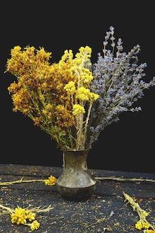 Herbes sèches fleurissent dans un vase - tutsan, sagebrush, origan, hélichryse, lavande.