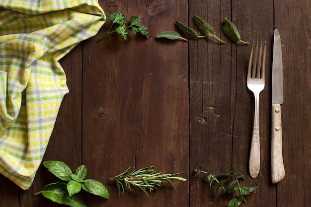 Herbes, serviette, fourchette et couteau sur une vue de dessus de table en bois