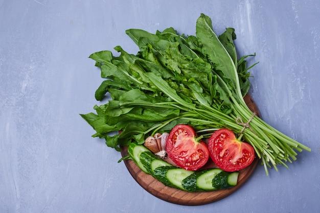 Herbes vertes et salade sur bleu