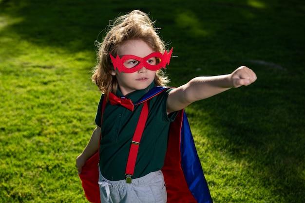 Héros de super-héros enfant étonné en cape rouge dans la nature.