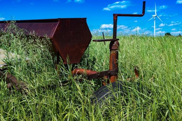 Herse à disques agricole vintage dans un champ entouré d'herbes hautes avec des éoliennes