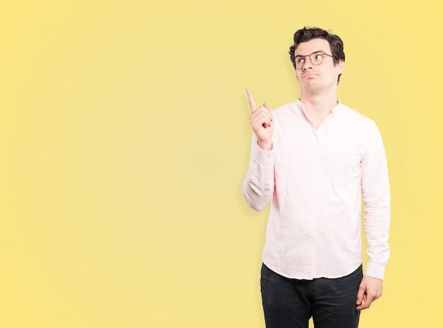 Hésitant jeune homme pointant vers le haut avec son doigt