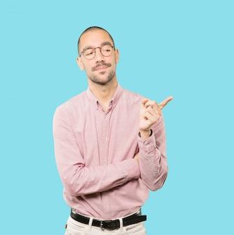 Hésitant jeune homme pointant vers vous avec son doigt
