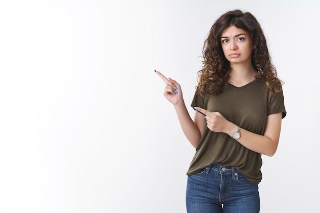 Hésitante mécontente méfiante intense fille arménienne mignonne ont un mauvais sentiment fronçant les sourcils moue douteuse pointant l'index gauche insatisfait, debout sombre insulté fond blanc