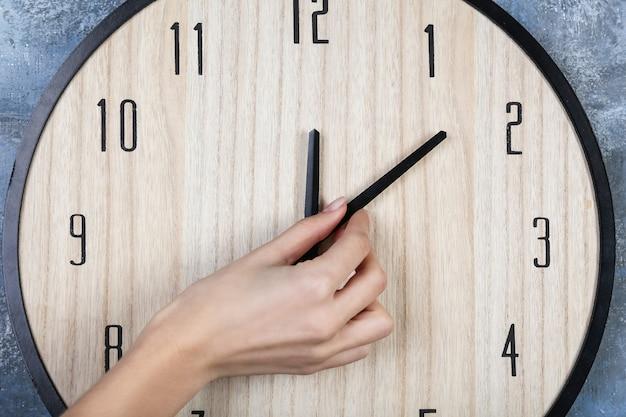 Heure de changement de main féminine sur grande horloge murale