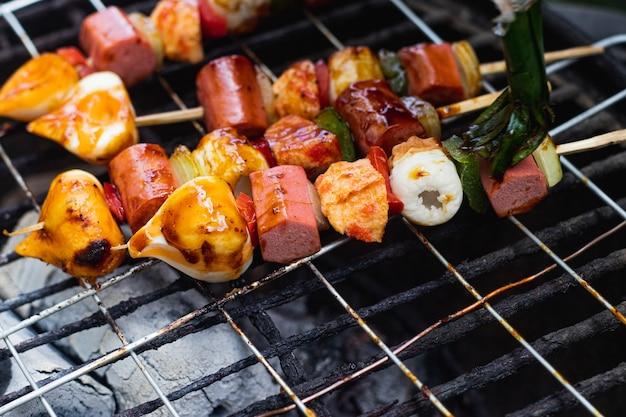 L'heure du barbecue avec des saucisses satay et des légumes au paprika grillés sur une plaque chauffante