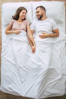 Heure du coucher. la famille dort. beau jeune couple amoureux est allongé sur le grand lit blanc et se repose. mari et femme ensemble au lit. photo vue de dessus