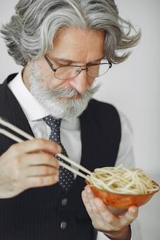 Heure du déjeuner. homme élégant au bureau. homme d'affaires en chemise blanche. l'homme mange des nouilles.