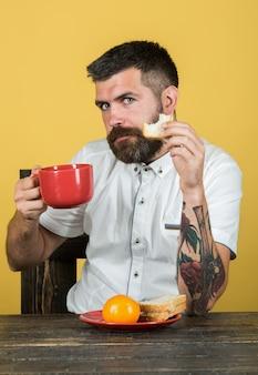 L'heure du déjeuner. petit-déjeuner déjeuner dîner. l'homme barbu mange de la plaque rouge. l'heure du café. matin. routine matinale.