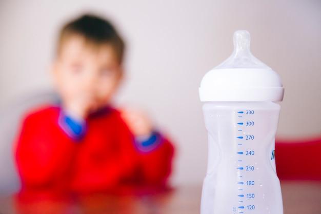 L'heure du déjeuner pour un petit garçon méconnaissable pour boire son lait