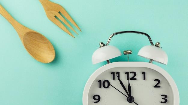 Heure du déjeuner avec réveil sur fond bleu.