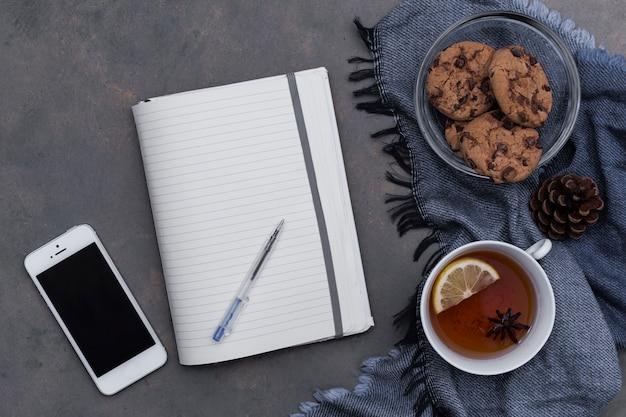 L'heure du thé avec des biscuits sur le plaid bleu avec le bloc-notes