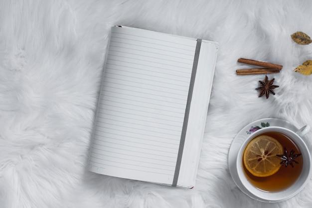 L'heure du thé avec un cahier vierge ouvert