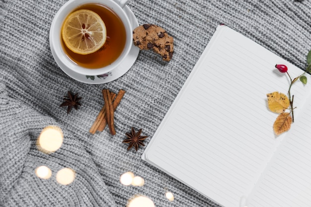 Heure du thé confortable avec un cahier sur un tricot