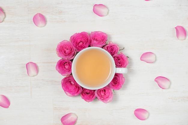 L'heure du thé. fond clair avec des fleurs et une tasse de thé.