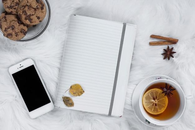 L'heure du thé sur un plaid avec un cahier ouvert et un smartphone