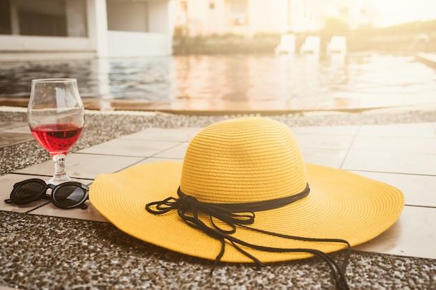 Heure d'été. chapeau, lunettes de soleil et verre de vin au bord d'une piscine