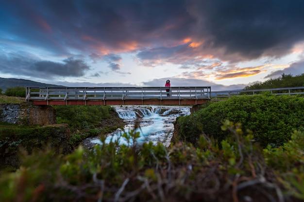 Heure d'été de la femme asiatique regarde à la cascade de bruarfoss en islande