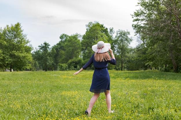 Heure d'été. femme au chapeau en robe blanche et bleue