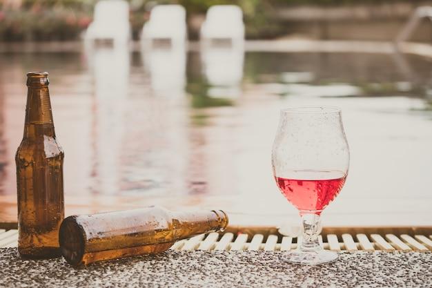 L'heure de la fête. bouteille de bière et de verre de vin à côté d'une piscine