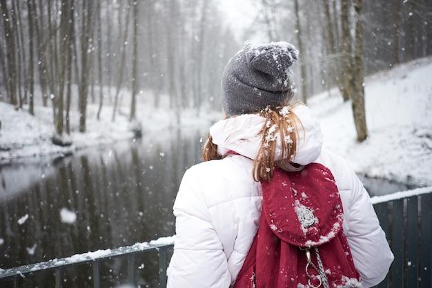 Heure d'hiver. première neige. jeune fille joyeuse attrayante, appréciant les chutes de neige.