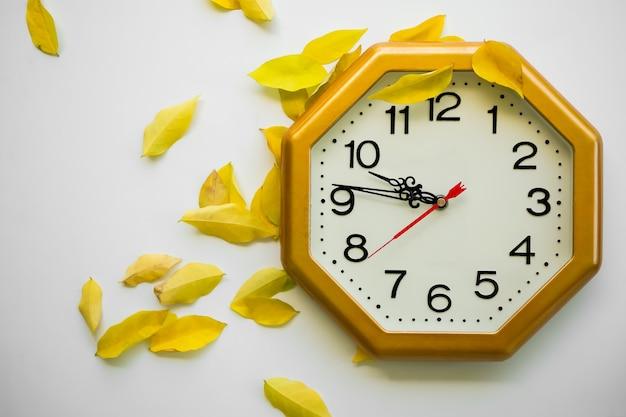 Heure de l'horloge avec des feuilles jaunes sèches sur fond blanc. mise à plat avec espace libre. saison d'automne, nouveau départ, les symboles demeurent, concept de solitude.