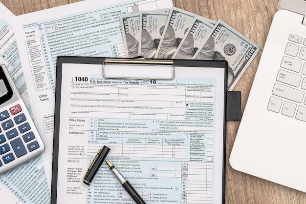 Heure de l'impôt. formulaire d'impôt 1040 avec stylo dollar et calculatrice