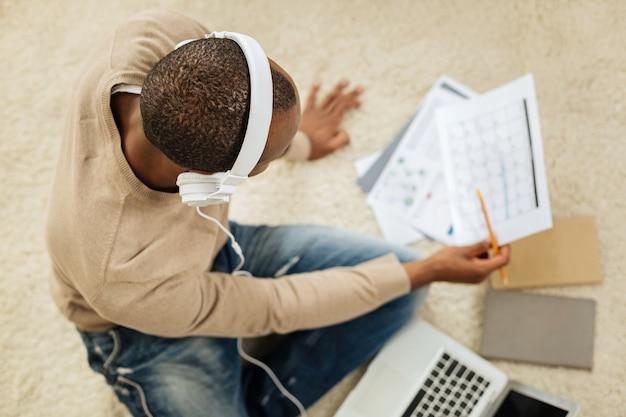 L'heure de la musique. homme afro-américain inspiré aux cheveux noirs, écoutant de la musique assis sur le sol avec son ordinateur portable et regardant des papiers