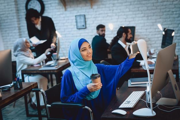Heure de pause au bureau, femme arabe handicapée, prise de selfie.